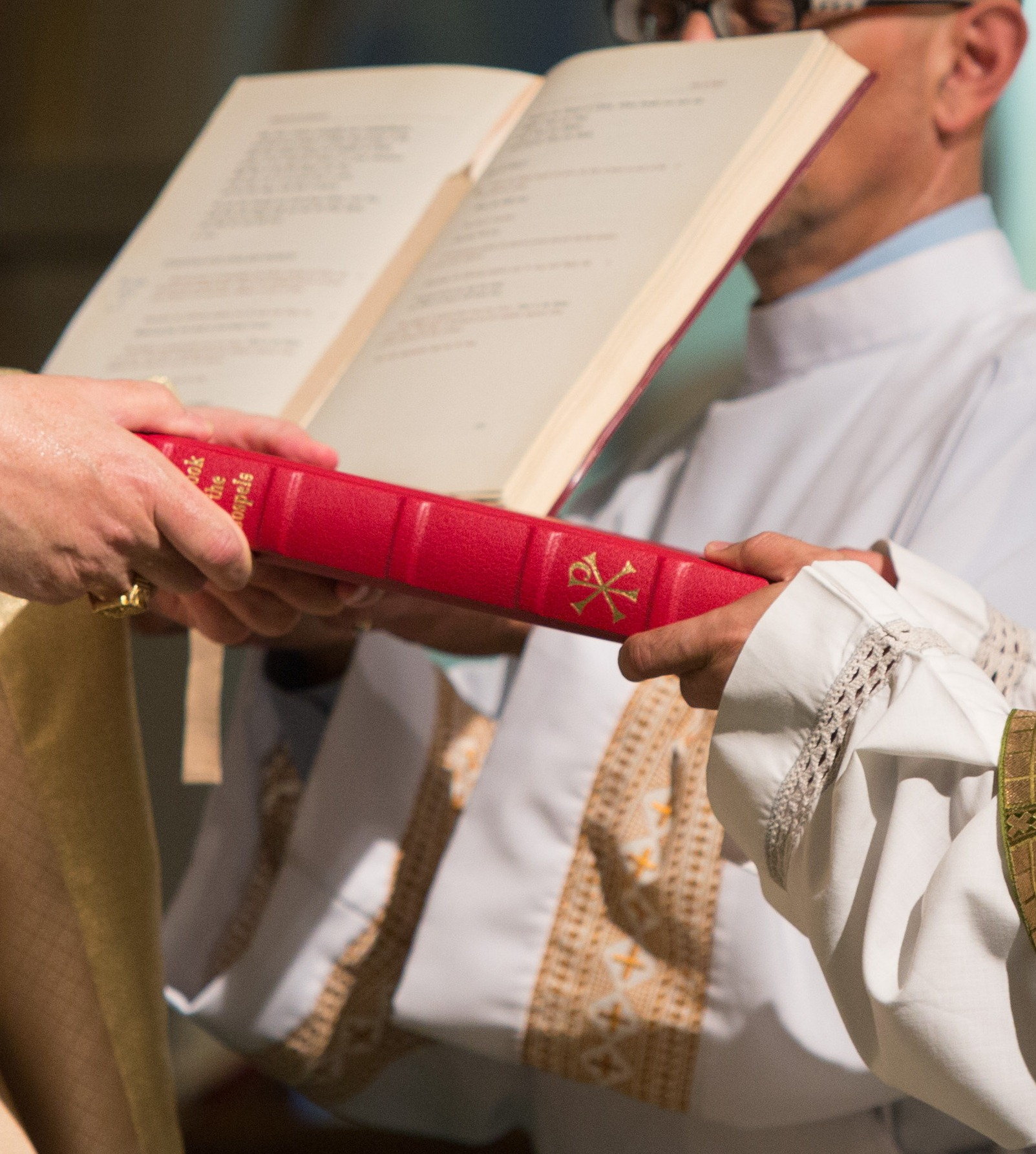 Picture shows newly ordained deacon receiving the Book of the Gospels